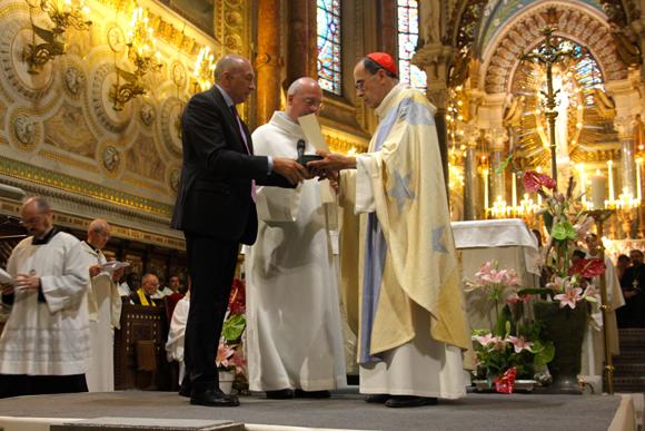 24. Gérard Collomb offre l'écu d'or frappé au soleil à la plus haute autorité ecclésiastique de la Ville, renouvelant le vœu des Échevins