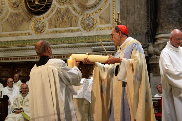 25. Beau symbole, la lourde charge en cire a été conjointement apportée à l'autel par une paroissienne de Vaise et une paroissienne de l'église de Mossoul.