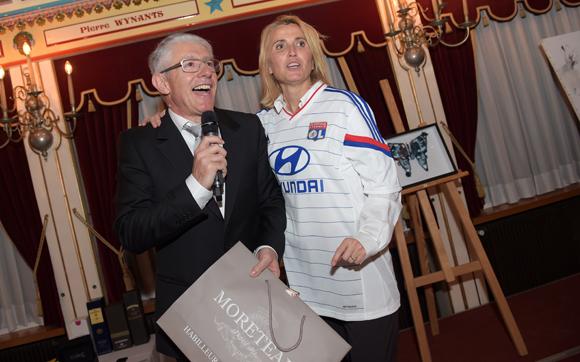 59. Elie Cunat (MBM Association) et le docteur Christine Dubost-Hocquart, portant le maillot de l'OL acquis par Nicolas Gagneux (6ème Sens Immobilier) et offert à Théo